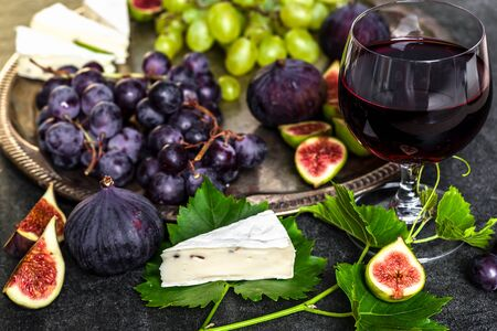 French food. Glass of red wine and snack set, plate with cheese, grapes and figs.