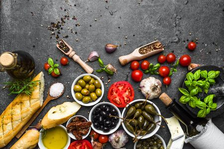 Italian food or mediterranean cooking ingredients. Herbs, olive, olil, tomato, bread, cheese and wine bottle.