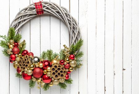 Christmas wreath on wood background with golden and red baubles and and christmas tree
