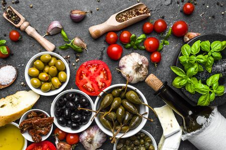 Mediterranean food on dark background: herbs, olive, olil, tomato, bread, cheese and wine bottle.