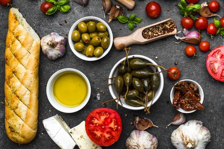 Italian food or mediterranean diet background. Cooking ingredients: herbs, spices, basil, tomato, olive, oil, bread.