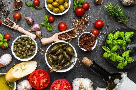 Sfondo di dieta mediterranea. Cottura degli ingredienti su ardesia scura. Archivio Fotografico