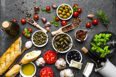 Mediterranean food background. Cooking ingredients on dark slate.
