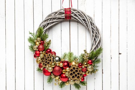 Golden and red composition of baubles on Christmas wreath on wood background