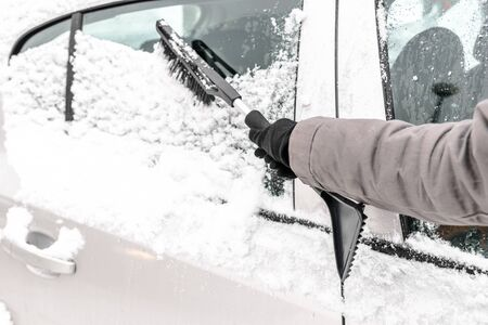 Woman cleaning car from the snow with brush. People in snowy cold weather in winter and transportation concept.