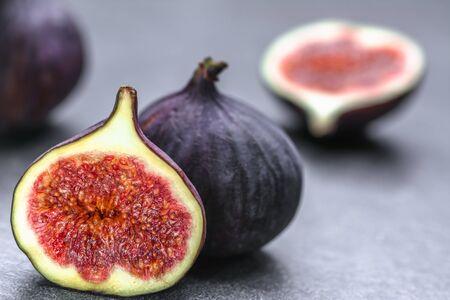 Frutti di fichi freschi. Fichi interi e affettati su sfondo scuro.