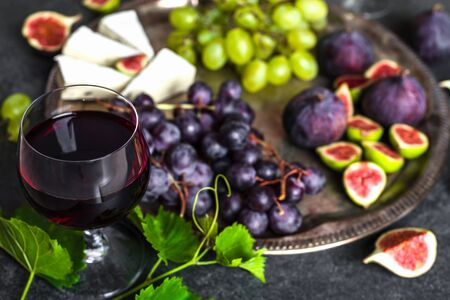 Glass of red wine with cheese, grapes and figs. French food on platter. 免版税图像