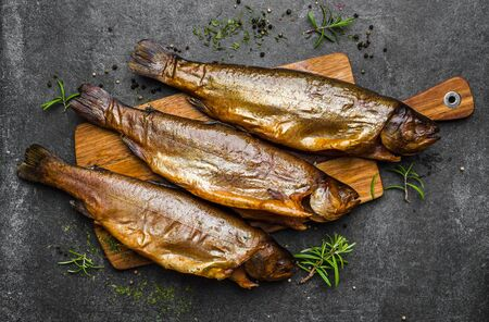 Smoked fish with spices on dark background