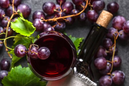 Fresh grapes, red wine glass and bottle, overhead Banco de Imagens - 133903347