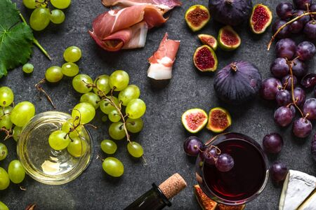 Buffet with wine snack set or appetizer. Italian meat, glasses of wines, cheese, grapes and figs.