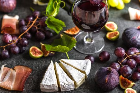 Buffet with wine snack set or french appetizer. Glass of red wine, cheese, meat and fruit. Banco de Imagens - 133903378