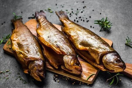 Smoked fish with spices on dark background Banco de Imagens - 133903381
