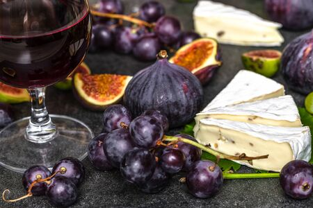 Wine and cheese tasting. Glass of red wine and food, french cheese, figs and grapes. Banco de Imagens