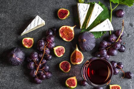 Glass of red wine with cheese, figs and grapes Banco de Imagens - 133903386