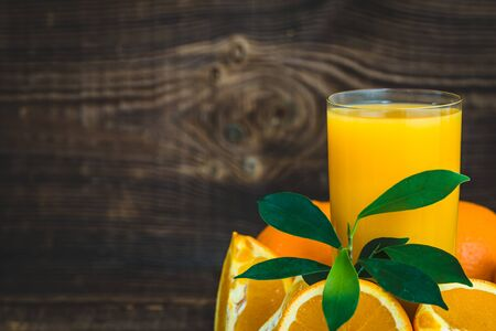 Freshly squeezed orange juice in a glass. Oranges and fresh juice on dark background. Banco de Imagens