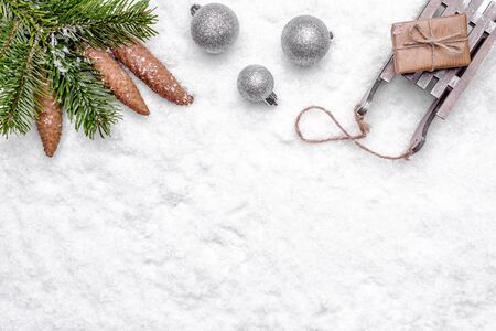 Christmas background with snow, christmas gift, ornaments, and fir tree branch, flat lay, top view Banco de Imagens