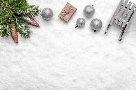 Christmas snow with composition, fir branch, ornaments and gift, christmas background