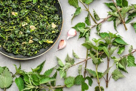 Cooking green vegetables. Healthy food, vegetarian pesto with green nettle and fresh stinging nettles, leaves fried with garlic and spices on frying pan.
