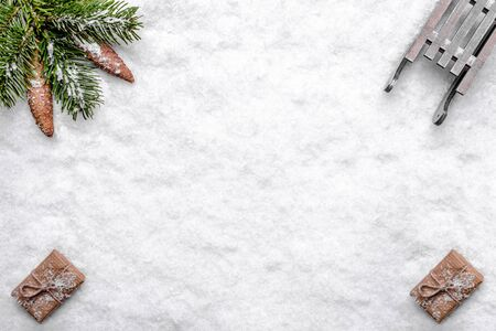Christmas white background with snow and composition with christmas gift boxes, fir branch, pine cones and sleigh