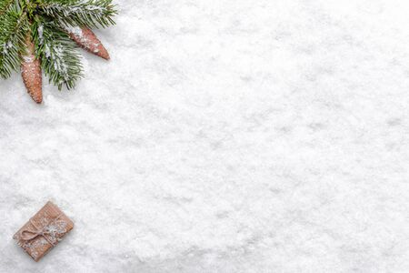 Christmas background with snow, christmas fir branch, pine cones and present box, flat lay, top view