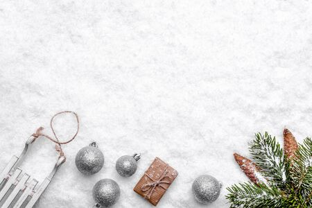 Christmas white background with snow and christmas composition, ornaments, gift box and fir branch with pine cones
