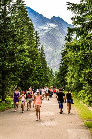 TATRA, POLAND - July 4, 2015: Polish Tatra Mountains, near Zakopane,  Group of tourists walking on road to Morskie Oko lake, Czarny Staw and Rysy in High Tatra Mountains, Poland