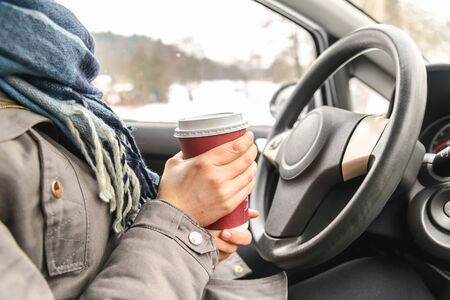 Driver drinking coffee in the car, driving and holding a steering wheel and cup of hot beverage at cold winter day with snow behind window
