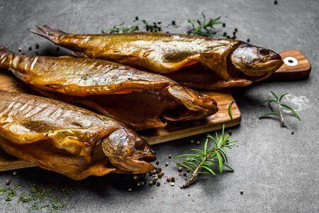 Pesce affumicato con spezie su fondo scuro