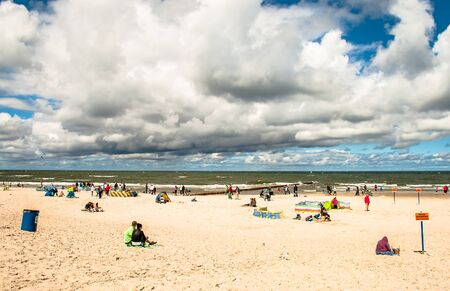 LEBA, POLAND - JULY 17, 2015: People enjoying at the beach in Leba city, bad weather, cloudy sky, Baltic sea, Poland Editorial