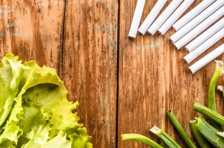 Cigarettes and vegetables arranged on grunge wood background. Concepts of quitting smoking. Choice between healthy lifestyle and unhealthy lifestyle.