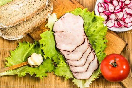 Healthy breakfast with meat, sliced ham and vegetables on kitchen table, top view