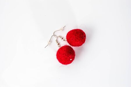 Felt earrings beads shaped. Handmade stylish felt jewelry made with red felt beads isolated on a white background. Imagens