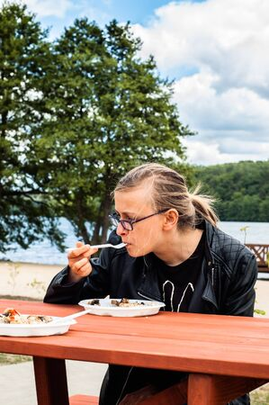 Woman tourist eats a meal at the lake surrounded by nature, summer holidays and vacation. Picnic by the lake.
