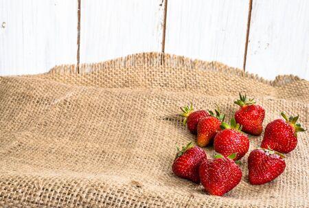 Fresh strawberries, ripe fruits on farmer market on rustic background
