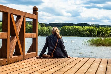 Landscape of wooden pier over beautiful lake in the summer. Rear view of a woman sitting on jetty surrounded by nature. Vacation and holiday time. Zdjęcie Seryjne