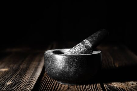 Pestle and mortar with black stone on wooden table Banco de Imagens