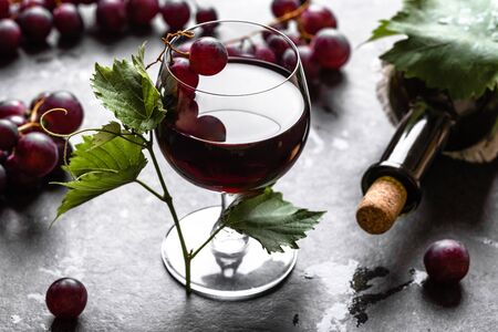 Bottle of wine and glass of red wine with grapes