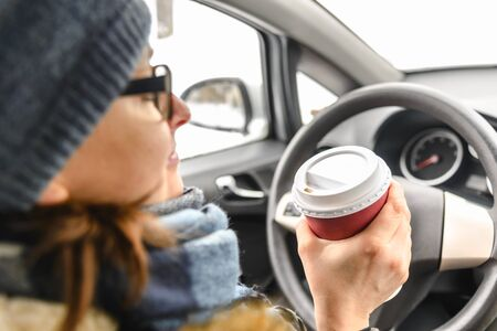 Beautiful woman in a car driving with coffee in hand in cold winter day Banco de Imagens