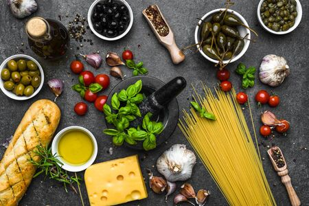 Italian food or mediterranean diet ingredients for cooking on dark background Banco de Imagens