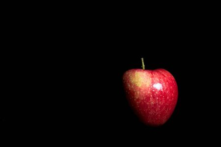 Ripe red apple on black background