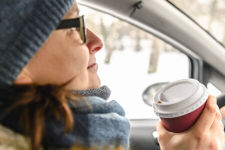 Woman driver drinking coffee in the car, driving and holding cup of hot beverage inside the auto in winter, snow behind window