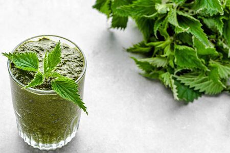 Healthy smoothie with green leaves of nettle in jar on white background