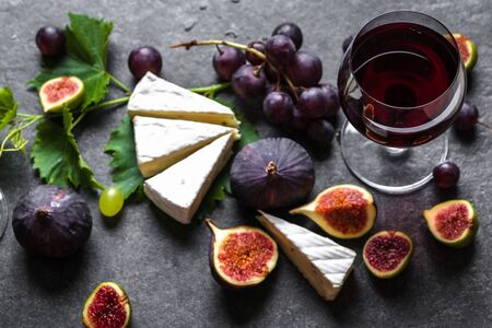 Brie cheese and wine. Appetizer and glass of wine, mediterranean snack, food background.