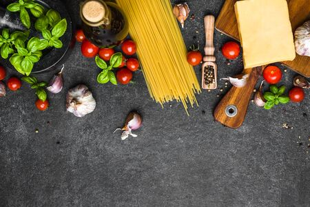 Italian food ingredients of spaghetti: tomatoes, basil, garlic, olive oil and parmesan cheese
