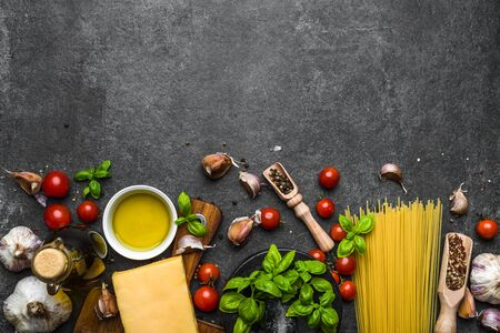 Italian food ingredients of spaghetti: pasta, tomatoes, parmesan, basil, olive oil, herbs and spices