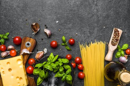Italian food ingredients of spaghetti bolognese: tomatoes, pasta, basil, cheese and spices Фото со стока