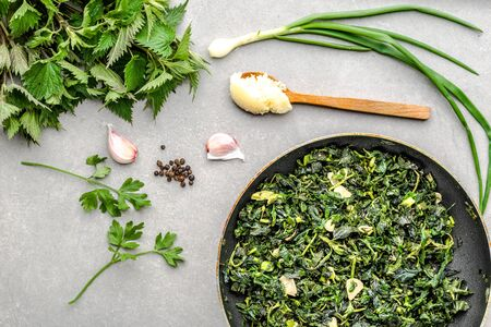 Cooking green food. Healthy, dieting, vegetarian pesto with green nettle and fresh stinging nettles, leaves fried with garlic and spices on frying pan.
