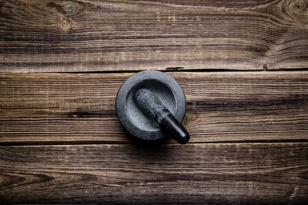 Black mortar with pestle on wooden table, top view