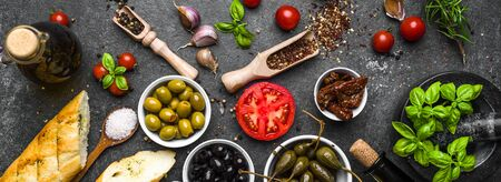 Mediterranean food background. Cooking ingredients on dark stone.