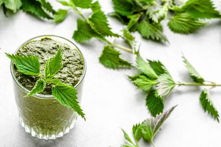 Glass of smoothie or green juice, detox drink with nettle leaves